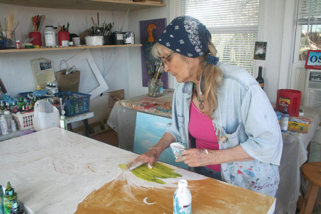Artist Margo Holst paints in her Crystal Beach studio. By DJ Kava.