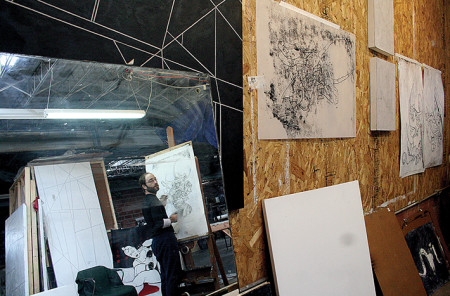 David Granitz is reflected in the mirror as he works in his studio space.