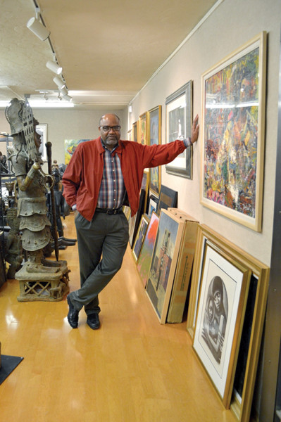 Dr. Hervy Hiner stands among his art collection in Port Arthur.