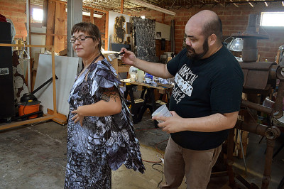 Maurice Abelman applies a layer to Melody Ann Boyd's Mother Nature avatar costume at his space in The Art Studio.