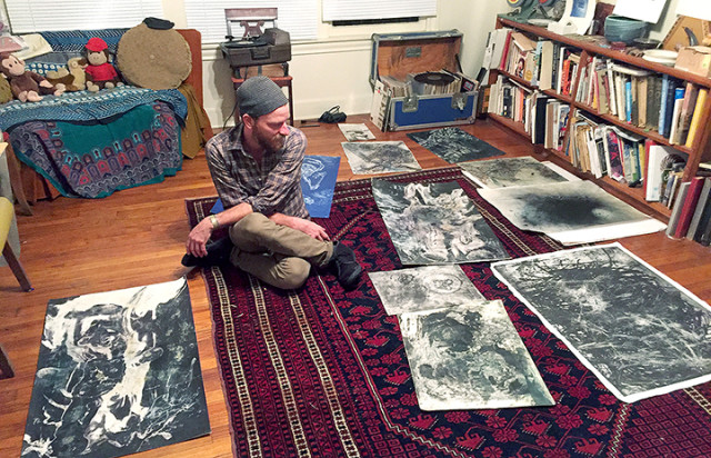 Artist Neal Pitak sits surrounded by his artworks in his home.