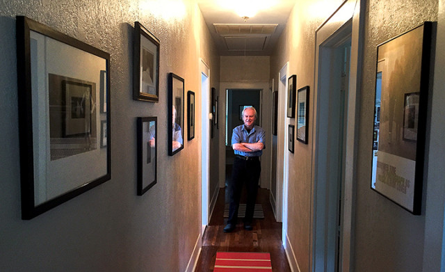 Dennis Kiel at home with his collection of photographs,